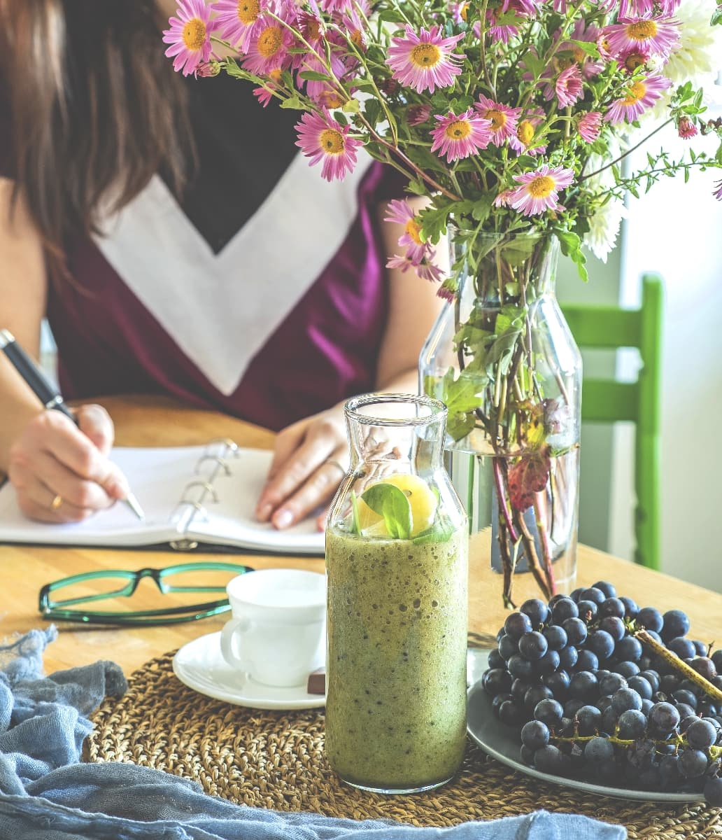 Young beautiful woman in the kitchen at the table writing in a notebook, breakfast business lady